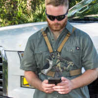 Man standing in front of truck with chest holster and cell phone