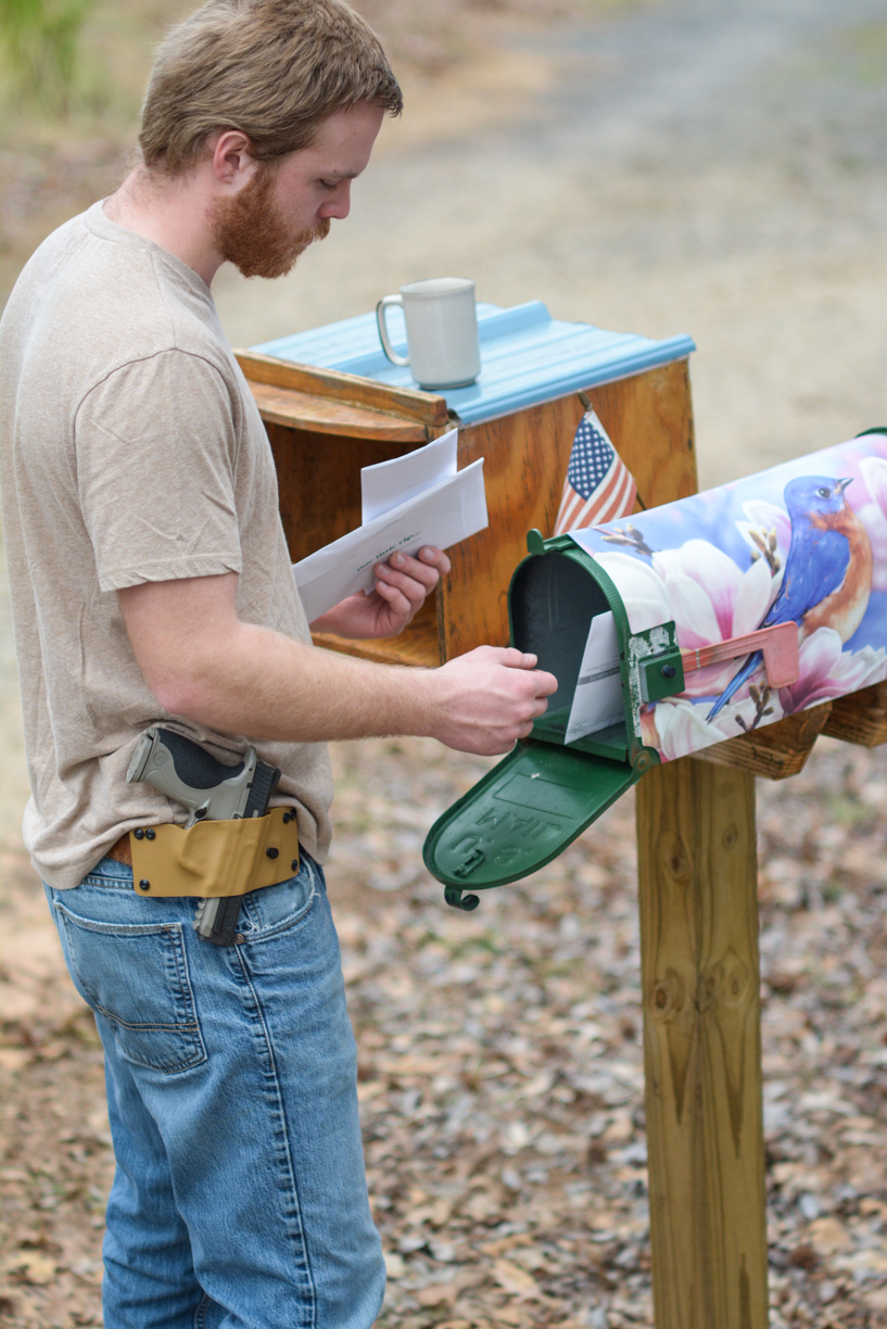 Man checking mailbox with kydex pancake holster on belt with weapon holstered.