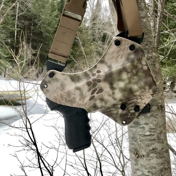 Chest holster hanging in tree with weapon.