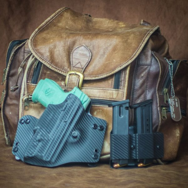 Pancake holster in carbon fiber kydex with double mag carrier in front of back pack.
